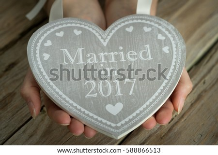 wooden heart with logo married in hands holding table sign grey  #588866513