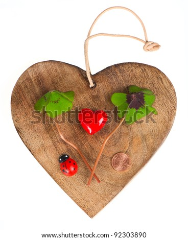 wooden heart with symbols of luck. red heart, coin, clover and ladybug