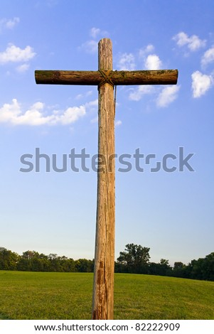 Wooden High Cross with blue sky and a few white clouds above a green landscape