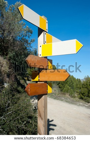 Wooden hiking trail signpost with multiple directions, signs empty for text