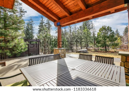 Wooden home exterior with spacious back patio, hot tub and barbecue. #1183336618