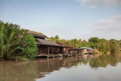 Wooden homestay floating on riverside in the evening at Amphawa, Ratchaburi, Thailand