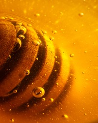 Wooden honey dipper with golden honey and air bubbles. Extreme close up