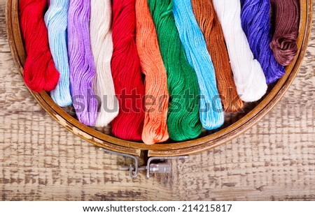 wooden hoop with threads for embroidery on wooden background
