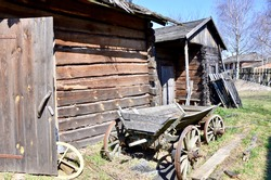 Wooden horse carriage in the bright rays of the spring sun. Old abandoned wooden house. Beautiful landscape with an abandoned wooden house and a wooden cart.