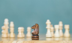 Wooden horse in chess game face with the another yellow team on sea blue background. Shot of a chess board brown horse moving with shallow depth of field.