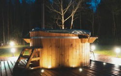 Wooden hot tub with fireplace at night.