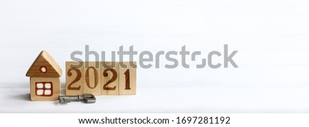 wooden house and a metal key with a fence and painted numbers. eco-friendly individual housing in 2021