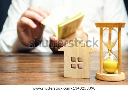 Wooden house and clock. Businessman counting money. Payment of deposit or advance payment for renting a home or apartment. Long-term mortgage on the house. Tax and mortgage vacations. Pledge