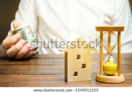 Wooden house and clock. Businessman holds money. Payment of deposit or advance payment for renting a home or apartment. Long-term mortgage on the house. Mortgage vacations. Buying and selling property