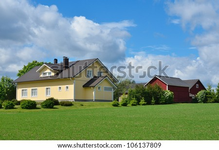 Wooden house and farm buildings in the countryside. Sunny summer day
