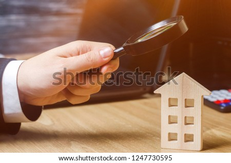 Wooden house and magnifying glass. Property valuation. Choice of location for the construction. House searching concept. Search for housing and apartments. Real estate concept. Home appraisal
