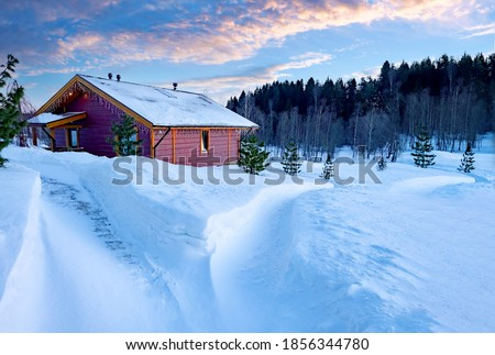 Photo of  Wooden house at edge of forest. One-storey cottage in winter weather. Single private house near forest. Country house. Trail goes to cottage in middle of snowdrifts. Cottage on a sunny winter day