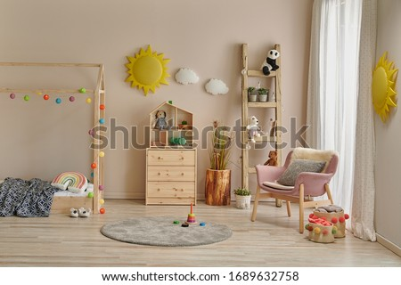 Wooden house bed detail cabinet and stair decor. Yellow sun and cloud decor. Pink chair in the room.