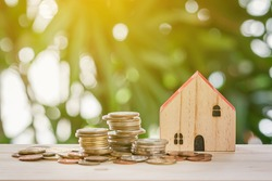 Wooden house designs and gold coins piled up on a wooden board with bokeh in the park.Save money for home buying and business loan recovery for real estate concepts. Refinance house