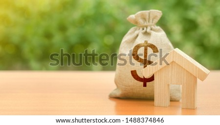 Wooden house figurine and a dollar money bag. Family budget, control and reduction of expenses. subsidized funds. Mortgage loan for purchase housing, construction or modernization. Tax, maintenance.