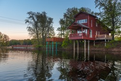 Wooden house in oak forest. Beautiful house in  twilight. Single family house. Vacation rental.