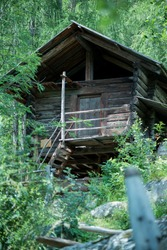 Wooden house in the mountains. Ancient structure. Shed in a woods.