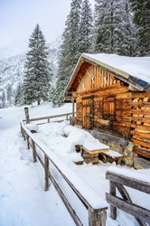 Wooden house in winter mountain landscape. Cottage / Hut in snowy mountains. Travel destination for recreation.