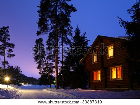 wooden house in winter wood in twilight