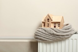 Wooden house model and scarf on radiator indoors, space for text. Heating efficiency