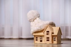 Wooden house model in hat on floor indoors, space for text. Heating efficiency