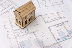Wooden house model on house plan, close up