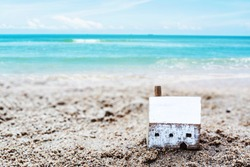 Wooden house model on the rock with blurred seascape background, Christian concept foolish man built house on the sand