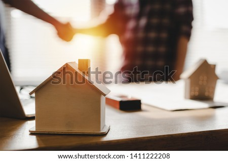 wooden house model on workplace desk with construction worker team hands shaking greeting start up plan new project contract in office center at construction site, partnership and contractor concept