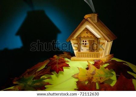 Wooden house on a hill covered with fallen autumn leaves nighttime scenic artistic still life
