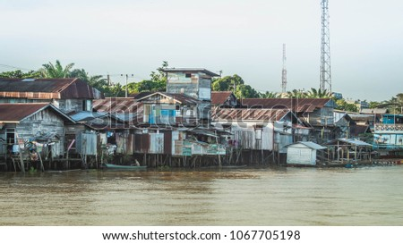 wooden house on the riverbank. slum area over the river. poverty and social problem concept #1067705198