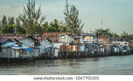wooden house on the riverbank. slum area over the river. poverty and social problem concept #1067705201