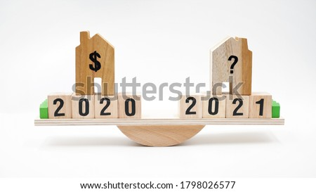 Wooden house with clock, business concept of housing market trends and property value. When is the best time to buy house or real estate investment after financial impact from coronavirus crisis.