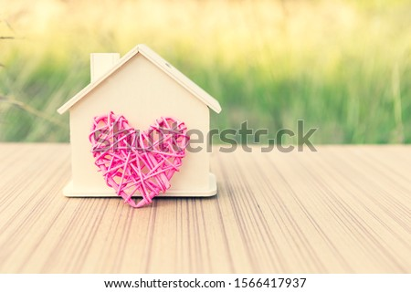 Wooden house with design wooden pink heart, house of love, vintage filter, outdoor day light stock photo