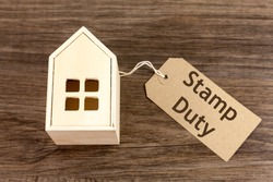 Wooden house with label attached which reads 'Stamp Duty'