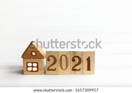 wooden house with light in the window and fence. house with a plot of 2021