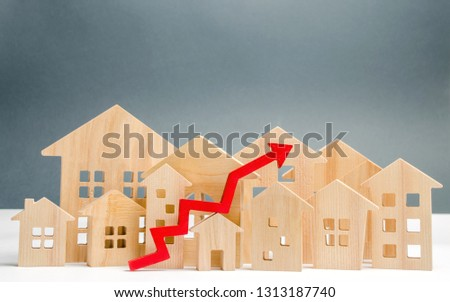 Wooden houses and up arrow. The concept of real estate market growth. The increased in housing prices. Rise price for utilities / rent. Increased demand for housing. Mortgage interest rates are rise