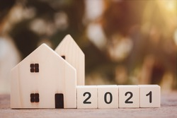 Wooden houses model with wooden block number 2021 and copy space using as background concept to save money buying house, new year property, business, real estate and property concept.