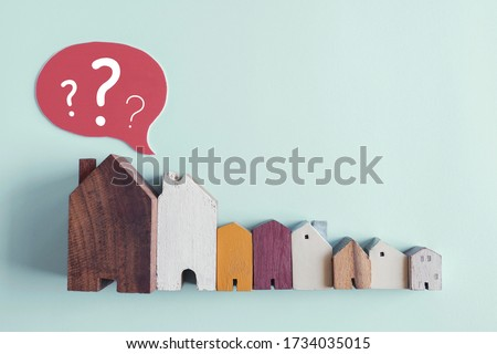 Wooden houses with question marks, housing crisis, confused decision, insecure investment, choosing right property concept