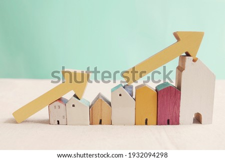 Wooden houses with yellow arrows up. housing boom, property market growing, high demand for real estate, house prices rising concept