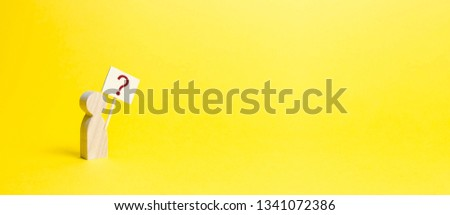 Wooden human figurine with a question mark. Minimalism. Asking a question, searching for truth and demanding truth. Curiosity, the desire to learn. The desire of man to improve. Banner