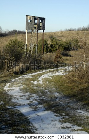 wooden hunting lookout, winter time, snow, dry grass
