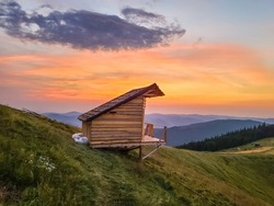 Wooden hut cabin on the Yavirnyk meadow in the Carpathians at sunrise.