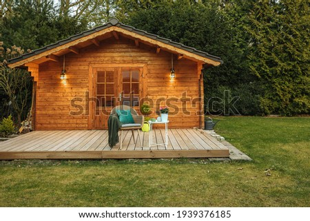 Wooden hut in spring. Drink tea in the garden when the weather is nice. Garden shed for vacation. Nice garden in Germany.  商業照片 ©