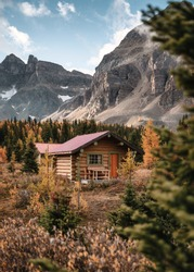 Wooden huts with rocky mountains in autumn forest at Assiniboine provincial park, Canada
