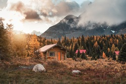 Wooden huts with sunshine in autumn forest at Assiniboine provincial park, Canada