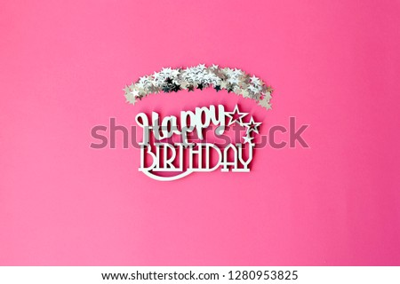 Wooden inscription happy birthday on a pink background.