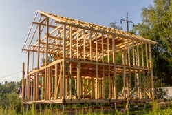 wooden interior frame of a new house under building, architectural residential construction stick built home framework.