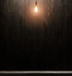 wooden interior room with classic Edison light bulb on wooden background switched on. retro edison light bulb