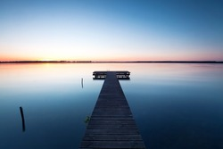 wooden jetty at lake, photographed in the evening, sunset in summer